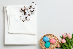 Top view of a stack of white bedsheets sets, cotton branch and a basket with Easter eggs. Copy space.