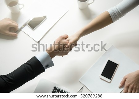 Top view of a strong handshake between man and woman, both sides viewpoints and interests have been considered. Effective negotiation with client. Business concept photo. Horizontal #520789288