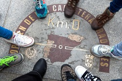 Top view of a symbol called Zero kilometre from Spain, with nine feet around. Place marked on the floor that is a sketch of the design of Spain, something symbolic.Popular meeting place Puerta del Sol