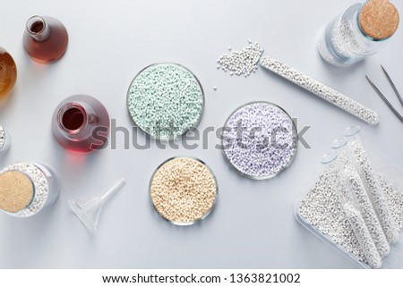 Top view of a table in a medical or manufacturing laboratory with chemical glassware and chemicals.