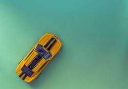 Top view of a toy car on a green paper texture