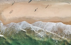 Top view of a tropical beach, surfers on the sand