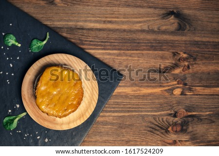 top view of a vegan burger with melted cheese on a wooden plate in a slate tray with green leaves, wood background, vegan food and healthy lifestyle concept