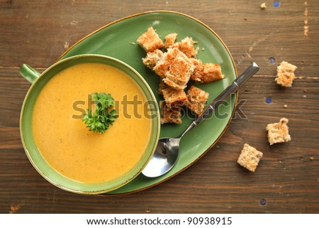Top view of a vegetable soup with bread and spoon