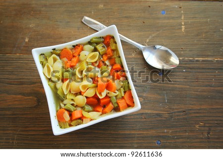 top view of a vegetables soup with spoon on a wooden table