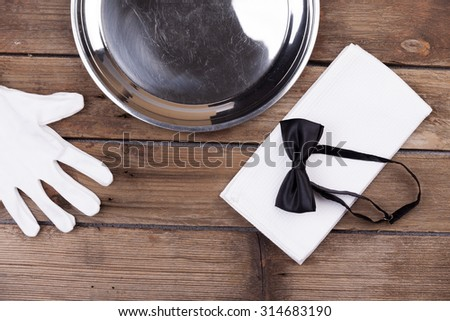 Top view of a waiter tray, bow tie, gloves and a napkin on wooden background