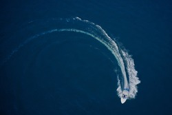 Top view of a white boat sailing in the blue sea. A boat with a motor on blue water in a turn. Top view of the boat. Aerial view luxury motor boat.