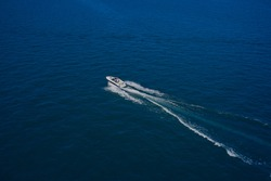 Top view of a white boat sailing in the blue sea. Aerial view luxury motor boat. A boat with a motor on blue water. Top view of the boat.