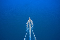 Top view of a white boat sailing in the blue sea. Drone view of a boat sailing at high speed. Aerial view of a boat in motion on blue water.