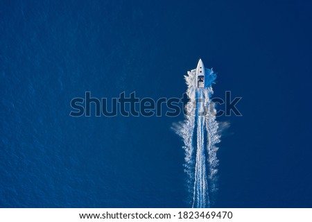 Top view of a white boat sailing to the blue sea. Large speed boat moving at high speed. Travel - image. Drone view of a boat sailing. Motor boat in the sea.