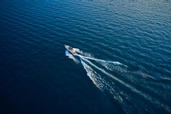 Top view of a white boat sailing to the blue sea.  Yacht in the rays of the sun on blue water.  Aerial view luxury motor boat. Drone view of a boat  the blue clear waters.