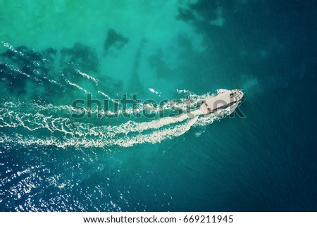 Top view of a white boat with people sailing in the blue sea  #669211945