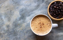 Top view of a white ceramic cup of Mocha coffee on a concrete table near a wooden bowl of coffee beans. Selective focus of a cup of coffee. Copy space.