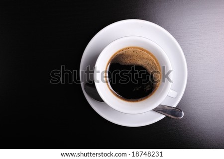 Top view of a white cup of coffee on black background