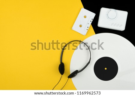 top view of a white long play vinyl record, black headphone and a white audio cassette tape with a white portable cassette player on the yellow and black background