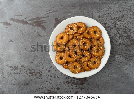Top view of a white plate filled with bite size bagel chips with assorted seeds on a gray background illuminated with natural light.