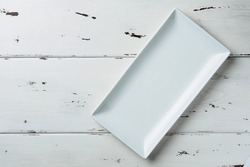 Top view of a white rectangular plate on a white wooden background. Flat lay. Copy space.