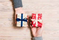Top view of a woman and a man exchanging gifts on wooden background. Couple give presents to each other. Close up of making surprise for holiday concept.