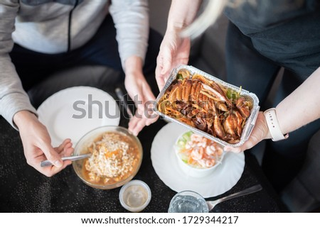 Top view of a woman holding a metal container with Chinese food and her partner ready to eat in unfocused background. Eating at home during isolation by Covid19.Family together