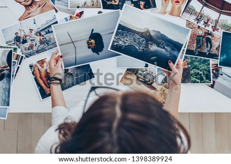 Top view of a woman photographer working in studio. Female photographer checking image prints.