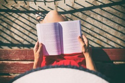 Top view of a woman reading a book.