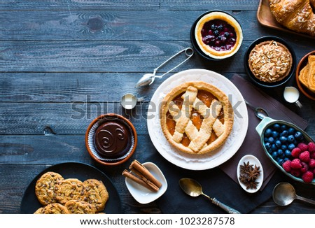 Top view of a wood table full of cakes, fruits, coffee, biscuits, spices and more breakfast classic sweet foods. #1023287578