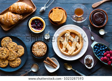 Top view of a wood table full of cakes, fruits, coffee, biscuits, spices and more breakfast classic sweet foods. #1023287593