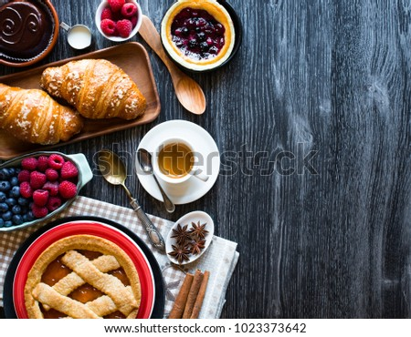 Top view of a wood table full of cakes, fruits, coffee, biscuits, spices and more breakfast classic sweet foods. #1023373642