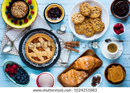 Top view of a wood table full of cakes, fruits, coffee, biscuits, spices and more breakfast classic sweet foods. #1024251883