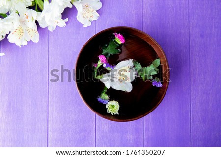 top view of a wooden bowl filled with water and white color alstroemeria flowers with statice on purple wooden background