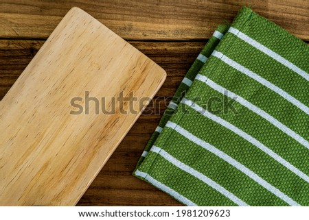 Top view of a wooden chopping board and a green kitchen tablecloth or napkin on a rustic wooden table. Rustic. Restaurant. Serviette. Dishware. Handmade. Stock photo ©