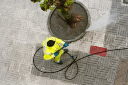 Top view of a Worker cleaning the street sidewalk with high pressure water jet. Public maintenance concept