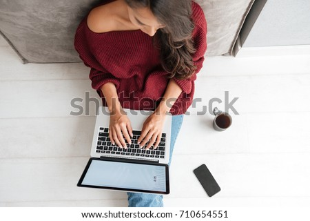 Top view of a young woman holding laptop computer on her lap while sitting at home #710654551