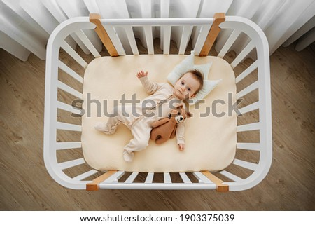 Top view of adorable infant in stylish pajama lying on pillow crown in comfortable cot at home. Baby with teddy bear in cradle in baby's room Foto stock ©