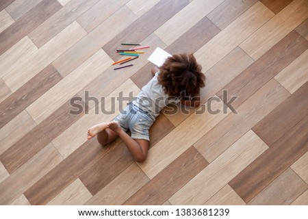 Top view of African American small girl lying on home floor painting with colorful pencils, black little kid relax having fun coloring picture in children colouring book, child entertainment indoors
