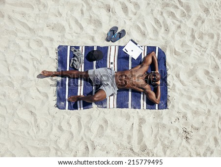 Top view of afro american young man relaxing on beach. Muscular guy wearing sunglasses and listening to music on headphones lying on a beach mat. Shirtless male model sunbathing.