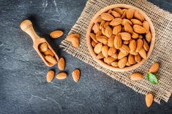 Top view of almonds on dark stone table with wood spoon or scoop. Almond in wooden bowl. Nuts freely laid on dark board.