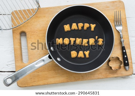 Top view of alphabet collage made of biscuits. Word HAPPY MOTHER'S DAY putting in black pan. Other kitchenware: fork, cookie cutter and chopping board putting on white wood table, vintage style image. - stock photo