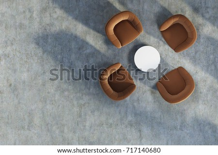 Top view of an office waiting area with four brown chairs standing near a round coffee table on a concrete floor. 3d rendering mock up
