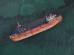 Top view of an old tanker that ran aground and overturned on the shore near the coast. A storm-swept old ship spilled oil and caused a major environmental disaster along the coast.