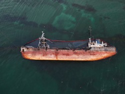 Top view of an old tanker that ran aground, overturned and polluted the coast with oil spilled from it. Ecological catastrophe.