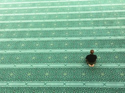 Top view of an unidentified Muslim man prays in a mosque