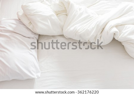 Top view of an unmade bed with a pillow, a bed sheet and a blanket after waking up in the morning.