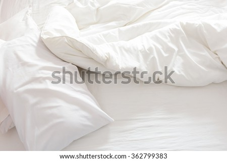 Top view of an unmade bed with crumpled bed sheet, a blanket and pillows after waking up in the morning. #362799383