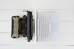 Top view of and old fashioned typewriter back-to-back with a modern laptop computer on w white wood desk.
