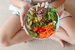 Top view of anonymous barefoot female showing bowl with healthy salad with vegetables and chicken meat