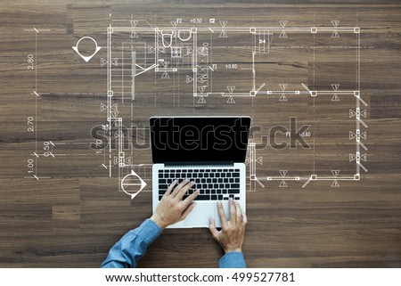 Top view of architect drawing on architectural project, businessman working on laptop computer PC on wood table, view from above
