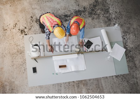Top view of architects and engineers to help create a blueprint to build a modern building equipped with the skills to fix errors and make suggestions during construction. stock photo