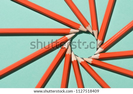 top view of arranged graphite pencils making circle on green