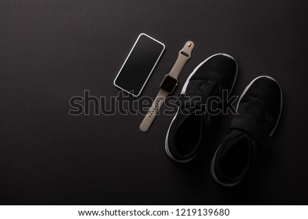 top view of arranged smartphone, smartwatch and sneakers isolated on black, minimalistic concept  #1219139680